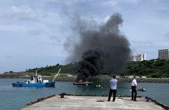 爆発後、船の後部から炎と黒煙が立ち上る遊覧船=午前10時20分ごろ、本部町の山川漁港(提供)