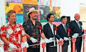開会式でテープカットするモンゴル800の(左から)高里悟さん、上江洌清作さん、儀間崇さんら=6日、那覇市おもろまちの県立博物館・美術館