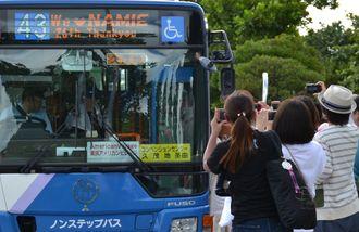 方向幕の「We♥NAMIE」の文字に歓喜し、撮影するファン=15日、宜野湾市