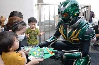 琉神マブヤー(右)から絵本や紙のお面などをもらう子どもたち=5日、那覇市・沖縄共同病院