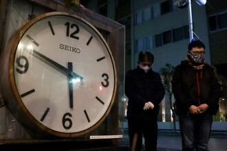 阪神大震災から26年となり、発生時刻で止まったままの大時計を囲み黙とうする人たち=17日午前5時46分、兵庫県西宮市