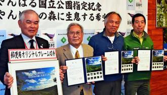 やんばる国立公園指定を記念したオリジナル切手をPRする宮城久和村長(左から2人目)ら=10日、国頭村役場