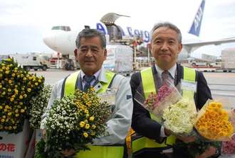 ANAの臨時便でキクを出荷した宮城組合長(左)とANAカーゴの高濱剛司沖縄統括室長=20日、那覇空港