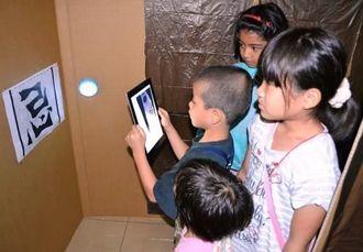 iPadに映る3Dお化けに見入る子どもたち=13日、那覇市・ひやみかちマチグヮー館