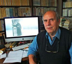 沖縄の地震観測記録の仏文書を発見したベイユヴェール博士。後ろの画面に映っているのがヒュレ神父の写真