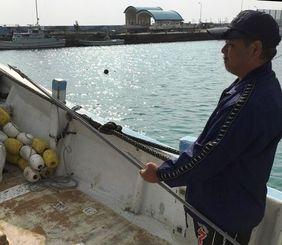 自身がヒートゥー漁で使う漁船の上で先のとがった銛(もり)を手にする漁師の岸本悟さん。形は昔の銛と同じだが形がコンパクトになり材質も軽くて丈夫な金属になっている。捕鯨砲なども使うという=名護漁港