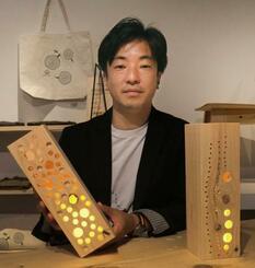 虫食い材で作ったスタンドライトを手にする榎本将明さん=4月、和歌山県田辺市