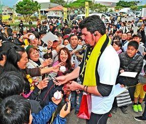 サインをもらおうと、阪神のメッセンジャー投手の周りを囲むファン=1日午後、宜野座村野球場(国吉聡志撮影)