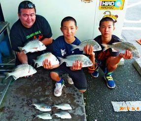 泡瀬海岸で41・5センチ、1・12キロのチヌなどを釣った大久保駿矢さん(中央)=4日