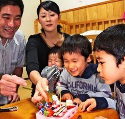 左から新垣裕己さん、妻の千歳さん、三男高大ちゃん、次男壮大ちゃん、長男裕大ちゃん。家族そろってクリスマスケーキを囲んだ=豊見城市