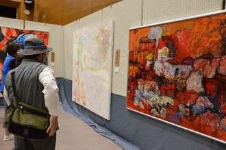 沖展会員などの入賞作品を鑑賞する来場者=6日、うるま市生涯学習・文化振興センター