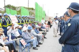 県警の機動隊と警備員に挟まれながら、辺野古新基地建設に抗議する市民ら=4日午後0時半、沖縄県名護市辺野古の米軍キャンプ・シュワブゲート前