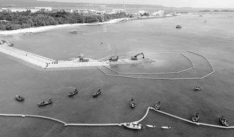 名護市長選後、2日目。キャンプ・シュワブ海岸では、新基地建設は着々と進む。「K2」護岸では、砕石を海に投入する作業が続いた=2月6日正午過ぎ、名護市辺野古の米軍キャンプ・シュワブ