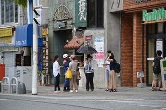 通行者に封鎖を説明する那覇市の職員ら=23日午前11時、那覇市・琉球銀行松尾支店前