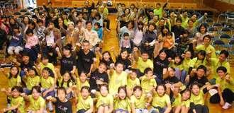 オープニングセレモニーで、「KIFFO」を合い言葉に腕を上げる子どもスタッフと来場者ら=26日、那覇市・若狭公民館