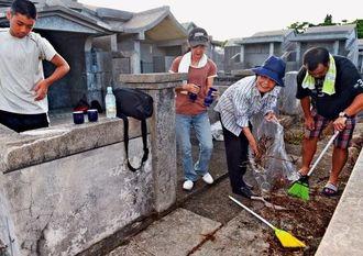 旧暦の七夕に合わせて墓の掃除に訪れた家族=20日午後、那覇市・識名霊園