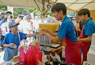 カーブチー100%のジュースを買い求める来場者ら=沖縄の産業まつり会場内のオキネシアのブース