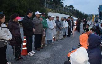 新基地建設に反対して座り込む市民らの前であいさつする市町村議ら(左)=13日午前7時20分ごろ、名護市辺野古の米軍キャンプ・シュワブのゲート前