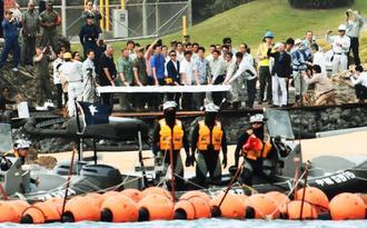 護岸工事開始直前、セレモニーに参加した日米の関係者。海保が厳重に警戒する中、一斉にボタンを押した=25日午前9時18分、キャンプ・シュワブ内のビーチ(阿部岳撮影)
