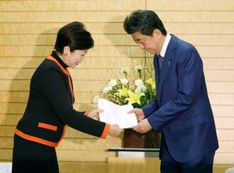 安倍首相(右)と面会し、新型コロナウイルス対策に関する緊急要望書を手渡す東京都の小池百合子知事=26日夜、首相官邸