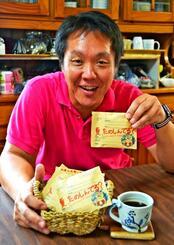 「送れるコーヒー」を販売するワーカーズホームの横山順一施設長。デザインは娘のしゅうさんが手掛ける=10日、宜野湾市大謝名