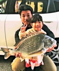 泡瀬漁港で52・2センチ、2・75キロのチンシラーを釣った稲嶺幸貴さん(後)と希幸ちゃん=12月18日