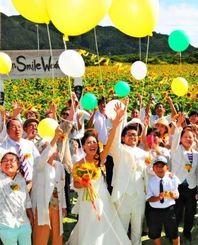 約15万輪のヒマワリに囲まれて愛を誓い、バルーンを飛ばす比嘉将寿さん(前列左から4人目)桜子さん(同3人目)夫妻ら=26日、石垣市川平真地原