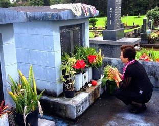 ハワイに移民した親族の墓前に手を合わせる高江洲福枝さん=ハワイ州ヒロ市