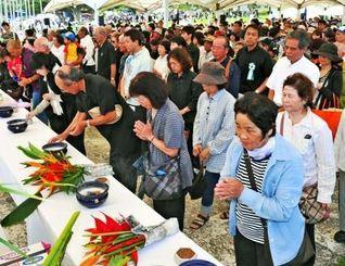一般焼香で戦没者の冥福を祈り手を合わせる参列者=23日午後1時すぎ、糸満市摩文仁・平和祈念公園