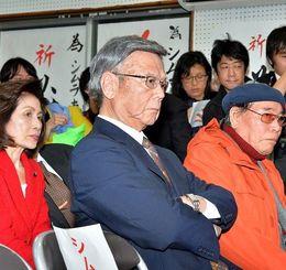 厳しい表情で宜野湾市長選を伝えるニュースを見つめる翁長雄志知事=24日午後8時50分、宜野湾市普天間の選挙事務所