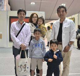 1万人目の来場者なった與儀清正さん(左端)一家。父・清孝さん(右端)の作品を見ようと家族で来場した=27日、浦添市民体育館
