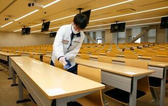 大学入学共通テストを前に、会場となる上智大四谷キャンパスの教室で行われた消毒作業=15日午後、東京都千代田区