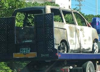 レッカー車に載せられる炎上車両=8日午後3時55分ごろ、沖縄自動車道の沖縄市八重島付近