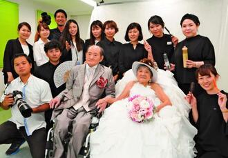 沖縄ワタベウェディングのスタッフたちに囲まれる勇吉さん(手前右から3人目)とトミさん(同2人目)夫婦=南城市・沖縄メディカル病院