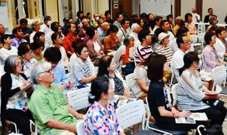 シンポジウム「多様性世界を生き抜く沖縄の力(レジリエンス)を求めて」でパネリストの講演に耳を傾ける来場者=11日、那覇市泉崎・県立図書館