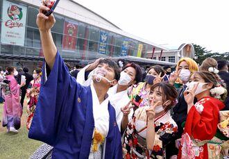 成人式終了後、友人たちと笑顔で記念撮影する平良響(左)=10日、沖縄市体育館(豊島鉄博撮影)
