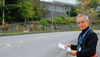 国頭農学校前にあった坂道を写真と比べる大城正也校長=2月19日、名護市大中