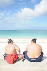 海をみながら日光浴を楽しむ男性たち=21日午後、宮古島市のパイナガマビーチ(仲田佳史撮影)
