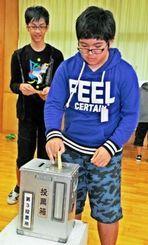 南城市PR大使を選ぶ模擬選挙で、投票や開票を体験した知念小学校の5・6年生=19日、南城市の同校