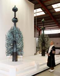 新調された国宝東塔頂部の飾り「水煙」を見上げる松久保伽秀執事。奥は奈良時代に作られた水煙=21日午後、奈良市の薬師寺