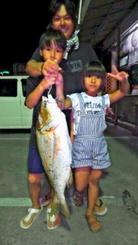 西原海岸で71センチ、4.39キロのタマンを釣った仲宗根英樹さん(中央)大陽さん(左)愛紗さん=9月30日