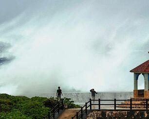 防波堤に打ち寄せ、高いしぶきを上げる波=8日午後0時40分ごろ、宮古島市城辺友利の博愛漁港(金子進通信員撮影)