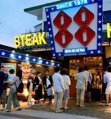 夕食時間、ステーキを求めて店内外で入店を待つ観光客ら=2日午後6時半すぎ、ステーキハウス88恩納店