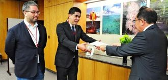 西銘恒三郎総務副大臣(右)から交付書を受け取る豊耕一郎社長(中央)=19日、総務省