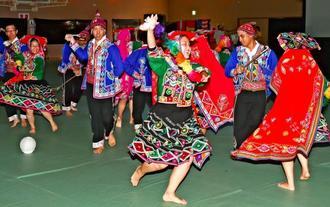 鮮やかな伝統衣装で民俗舞踊「ワイノ」を踊るペルーの県系人たち=21日、中城村民体育館(渡辺奈々撮影)