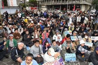 登壇者のあいさつに聞き入る集会参加者=29日午後2時13分、宜野湾市役所前