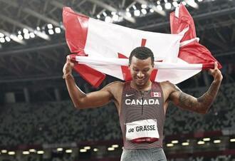 男子200メートルで優勝し、国旗を掲げるカナダのアンドレ・ドグラス=国立競技場