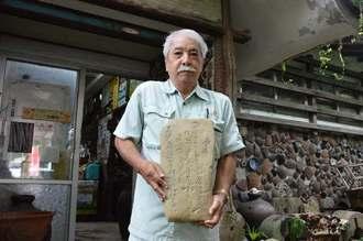 「康煕」の文字が刻まれている「石碑」の情報提供を求める諸見民芸館の伊礼吉信館長=沖縄市諸見里