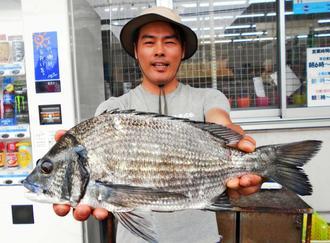 42・5センチ、1・12キロのミナミクロダイを釣った親泊健さん=8日