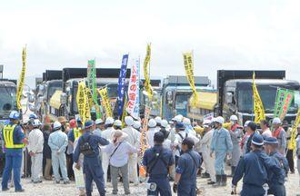 土砂を積んだダンプカーを止めようと車両の前に立ちふさがる市民を取り巻く警備員や沖縄防衛局職員ら=25日、本部港塩川地区